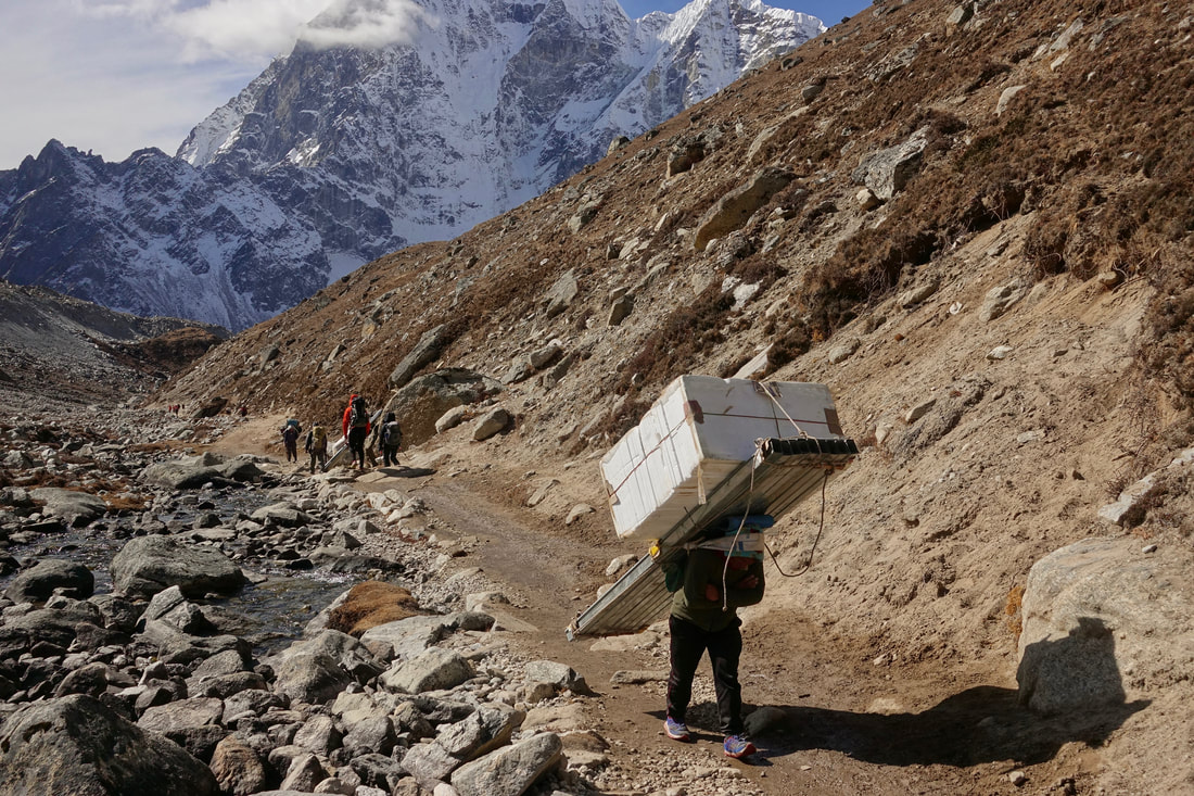 Porters carrying heavy loads to Everest base camp