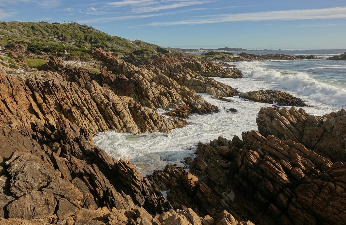 Walking along the West Coast of Tasmania along the rocks